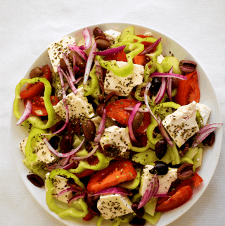 Greek Salad served in a shallow dish and made with big chunks tomatoes, cucumbers, feta cheese, olives, peppers, red onions etc