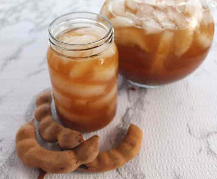 Homemade Tamarind Agua Fresca. Picture shows a glass with Tamarind Agua Fresca, a pitcher in the background and some tamarind pods.