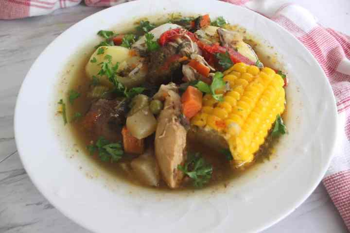 A plate of Bolivian Picana (Christmas Soup) - plate shows corn, chicken, beef, vegetables and is decorated with chopped parsley.