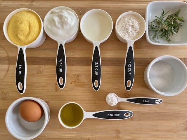 Visual representation of all the ingredients I used to make this Mediterranean Rosemary Cornbread - cornmeal, yogurt, milk, flour, rosemary, egg, olive oil, baking powder and salt/sugar.