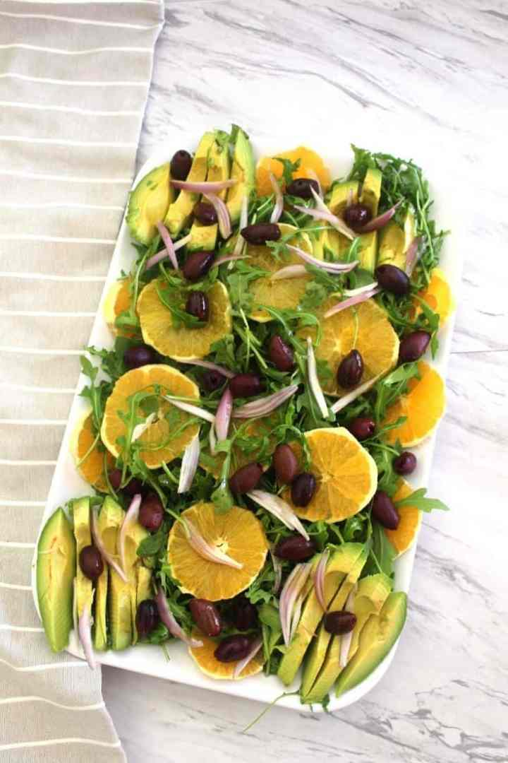 Delicious winter salad made with navel oranges, arugula, kalamata olives, red onions and avocados served with a citrus dressing.