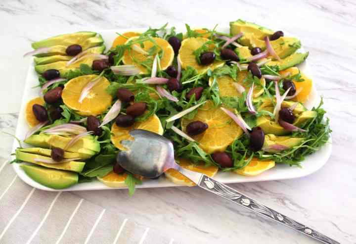 Orange salad with kalamata olives and red onions over arugula. This Mediterranean salad is served with an orange dressing.