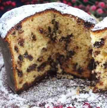 Homemade Christmas Sweet Bread, Panettone. Picture shows a panettone already sliced open, focusing on 3/4 of the bread. Bread is covered in confectioner sugar.