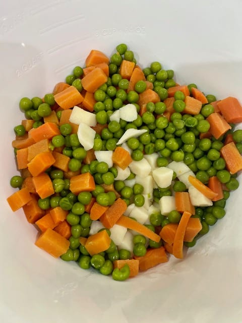 Diced potatoes, carrots and green peas in the salad bowl.
