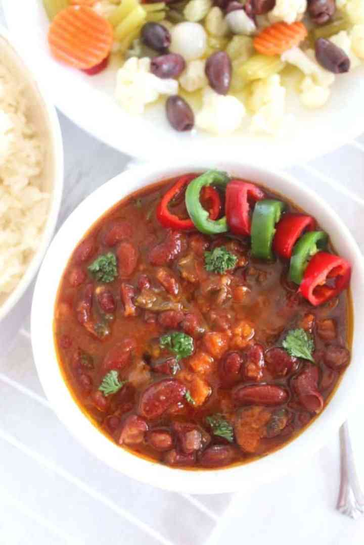 A bowl of red kidney beans soup shown as the focus of the picture, while on the sides you can see rice and a salad with pickled vegetables.