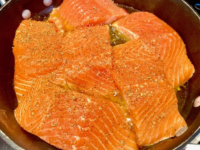 Seasoned salmon fillets cooking in a skillet with extra virgin olive oil.