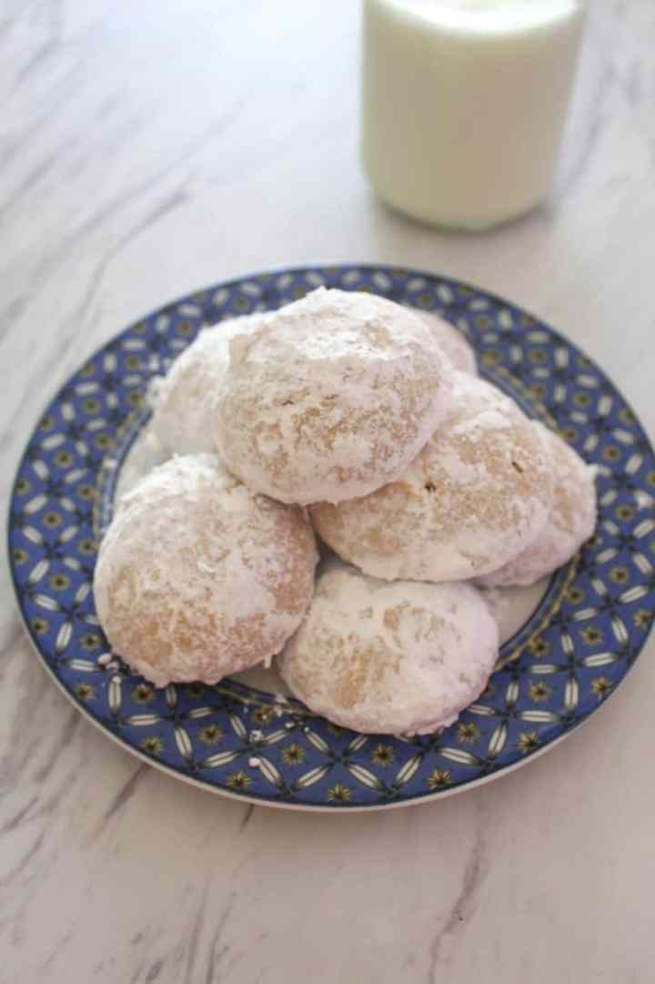 A plate of almond cookies covered in confectioner's sugar next to a glass of milk.