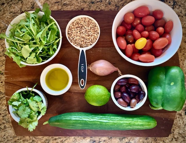 Farro Salad Ingredients - farro, shallot, extra virgin olive oil, green bell pepper, arugula, cilantro, english cucumber, kalamata olives, tomato medley, lime.