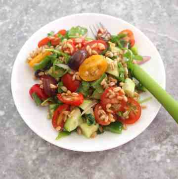 A plate of farro salad with grape size medley tomatoes, cucumbers, green peppers, red onions and kalamata olives.