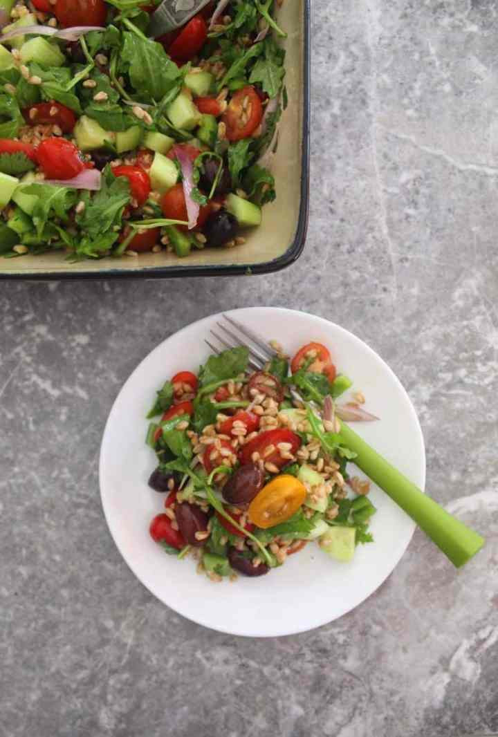 Healthy Mediterranean Farro Salad - picture shows a serving of the farro salad next to the salad bowl.