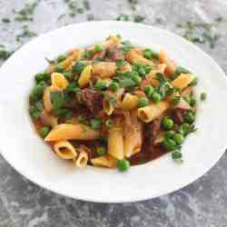 A plate with pasta, meat, green peas and parsley in a red sauce. This dish is called Aji De Fideos in Bolivia.
