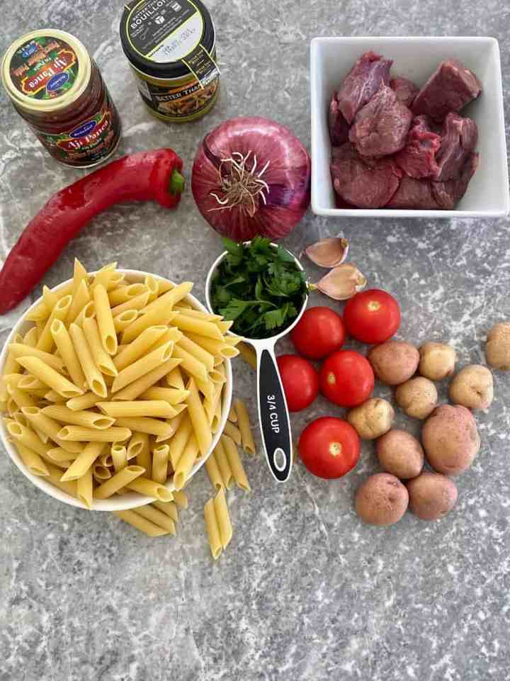 Ingredients to make the pasta dish all layed out, ready to cook: Aji Panca, Bouillon, red pepper, red onion, parsley, garlic, meat chunks, penne riggati, tomatoes, potatoes.