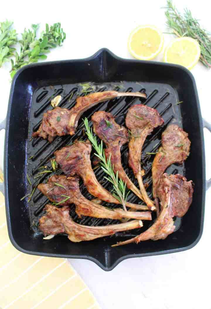 Lamb chops on cast iron pan, decorated with rosemary. Picture is styled with some fresh lemon, rosemary and oregano on the side of the pan.