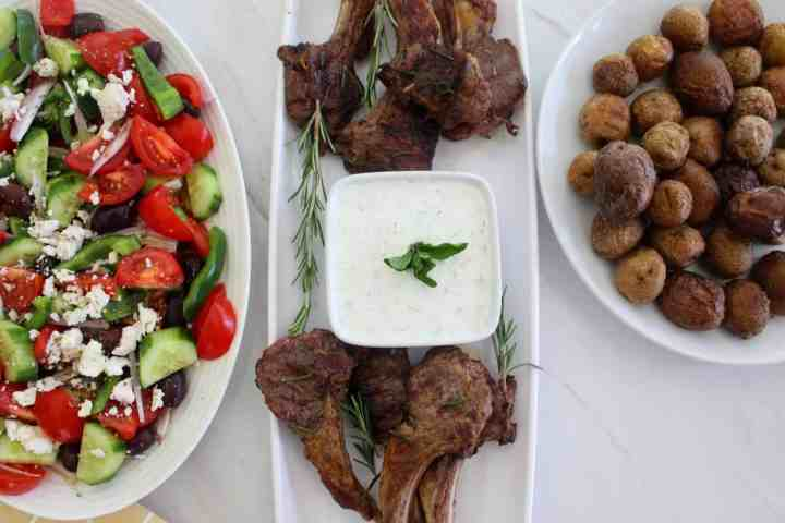 A platter of lamb chops, about 4 on each side with a tzatziki dip in the middle. On one side of this platter, you see a Mediterranean salad and on the other side you see roasted potatoes.