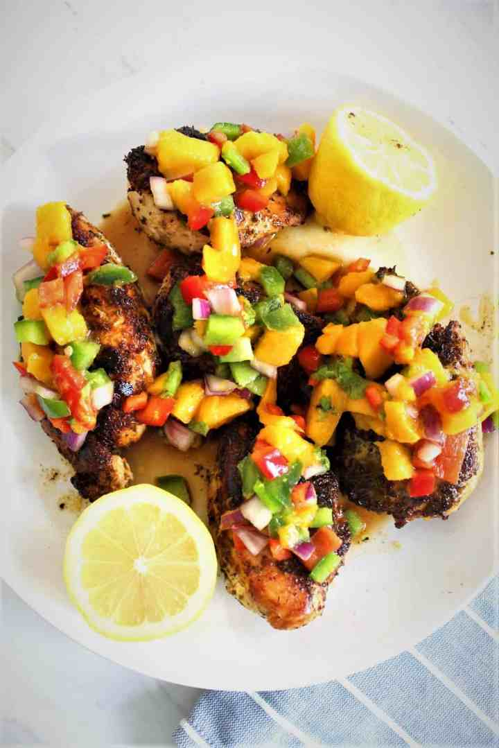 Skillet Chicken in Mango Salsa - picture shows a large round plate with cooked chicken topped with a mango salsa. There are 2 lemon halves in the plate too.