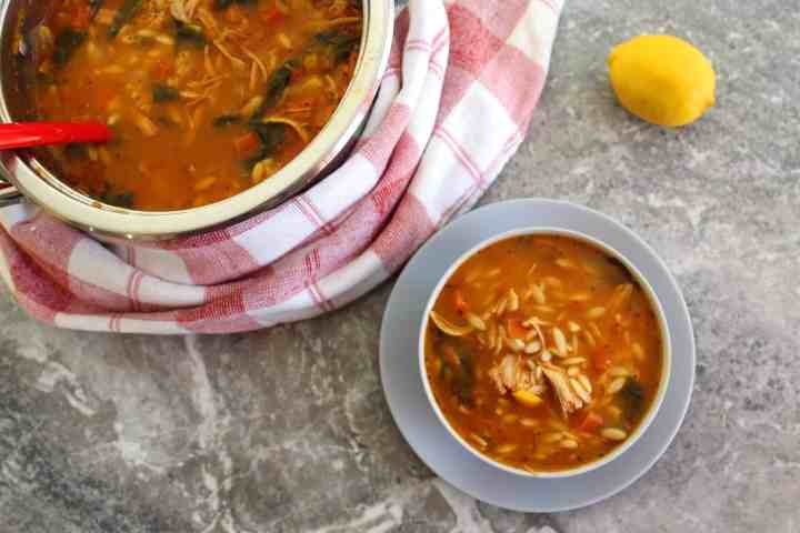 Orzo soup with shredded turkey and spinach!! Picture shows a bowl of the soup already served, the pot where it was cooked with a ladle in and a lemon on the other side.