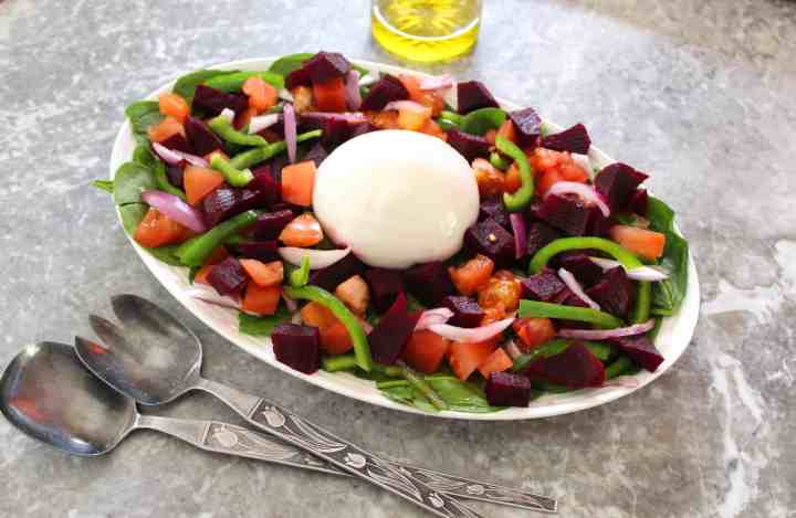 Sideways shot of a beets, burrata salad shown next to serving utensils and olive oil dispenser.