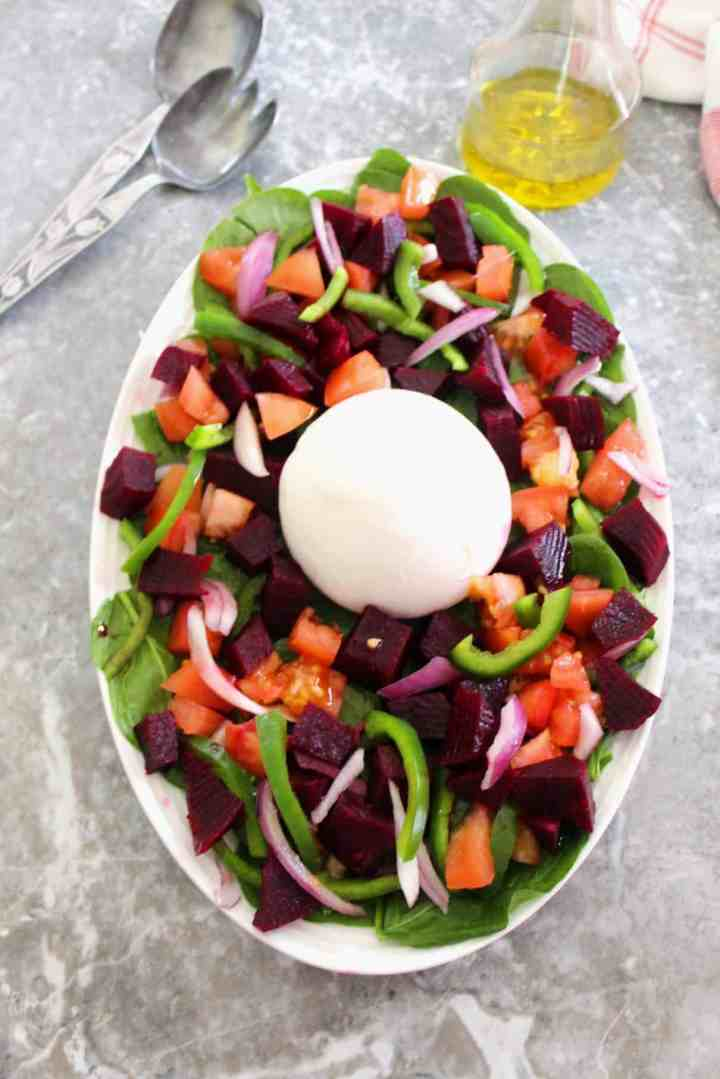 Oval salad platter with lots of colorful vegetables, topped with a burrata.