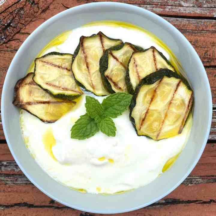 A bowl of yogurt soup with zucchini, olive oil and mint. Bowl is shown on some rustic surface.