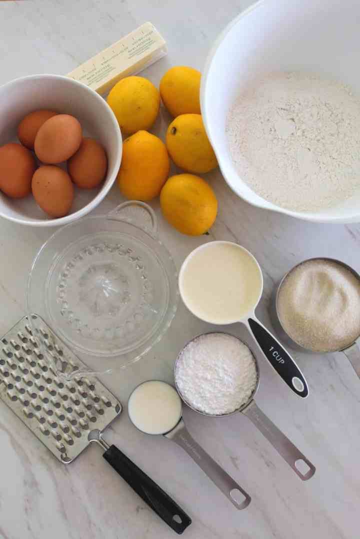 Ingredients in measuring cups and bowls for making Meyer Lemon Bundt cake - eggs, butter, flour, heavy cream, sugar, powder sugar, milk.