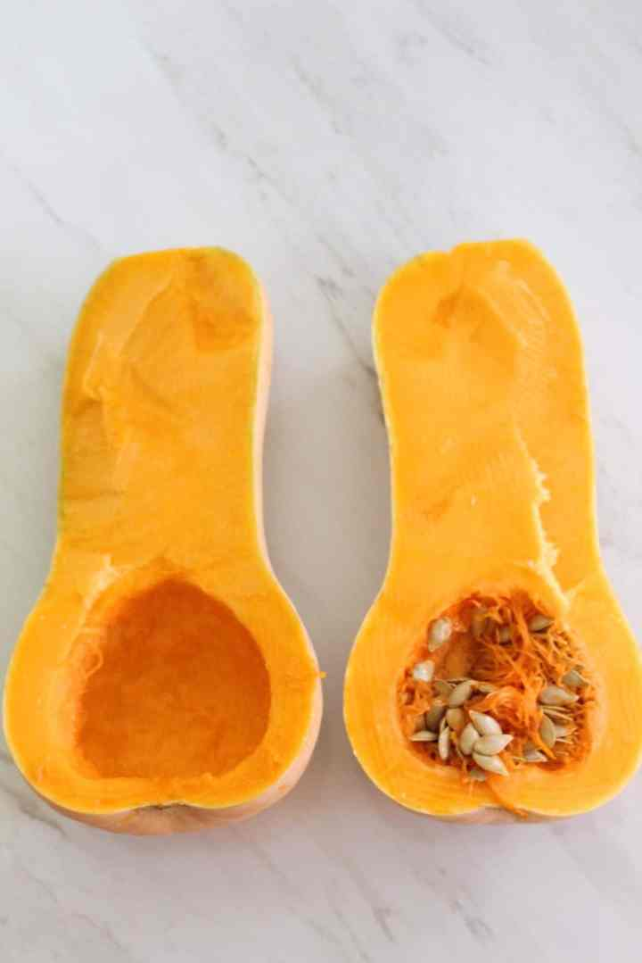 A butternut squash cut in half, one half is already cleaned from seeds and pulp but the other half not.