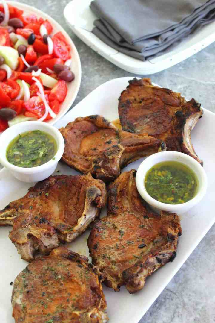 Seared pork chops with mint chimichurri and salad.