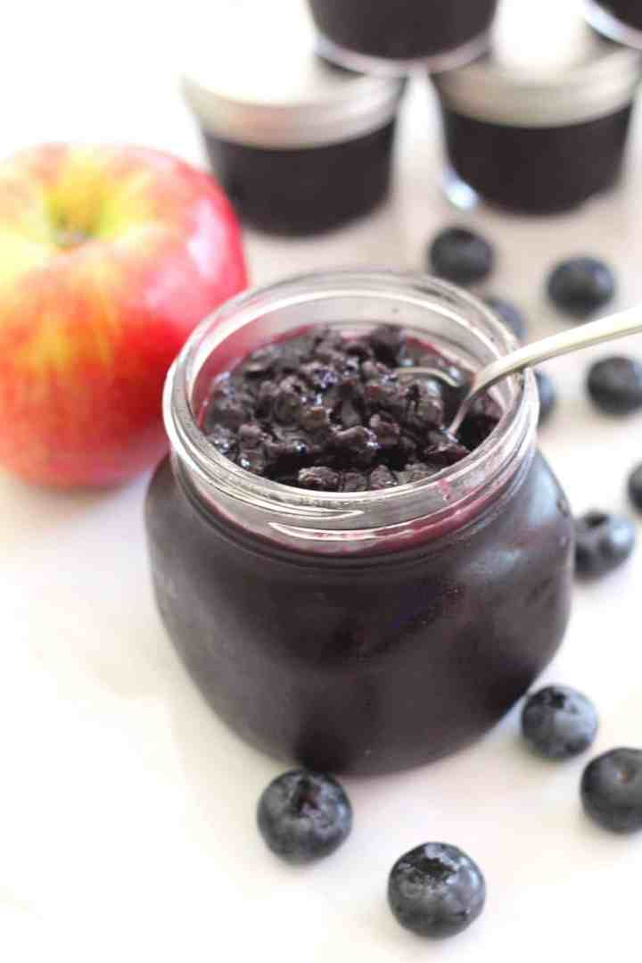 A spoon coming out of blueberry apple jam jar full of jam. In the background you see an apple and jars of jam!