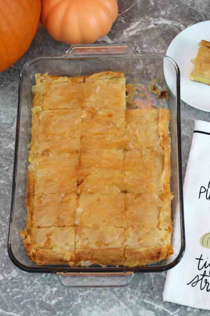 A baking tray with a phyllo baked dish, with a pumpkin towel next to the tray. A slice has already been cut out of this tray.