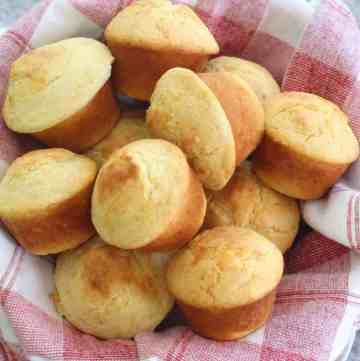 Cornbread muffins filled with cheese, over a serving basket lined with a napkin