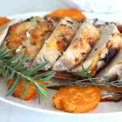 A platter with roasted turkey breast, sweet potatoes and fresh herbs.
