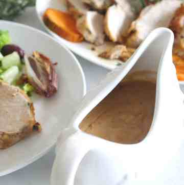 A gravy serving bowl with gravy in it, shown next to a plate of served food and another platter with sliced turkey.