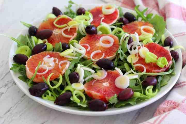 An orange salad, shown sideways. Ingredients visible on the salads are olives, leeks, greens and blood oranges sliced in circular shape.