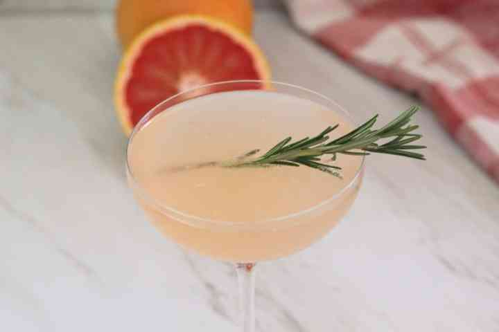 A coupe glass with a pink cocktail made with elderflower syrup, prosecco and grapefruit.