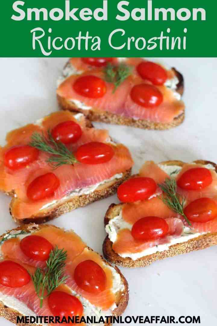 An image prepared for Pinterest. It shows the smoked salmon crostini in the center, a title bar on top of the picture and a website link at the bottom.