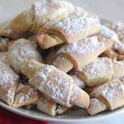 Soft jam filled cookies in crescent shape. They're covered in confectioner's sugar.