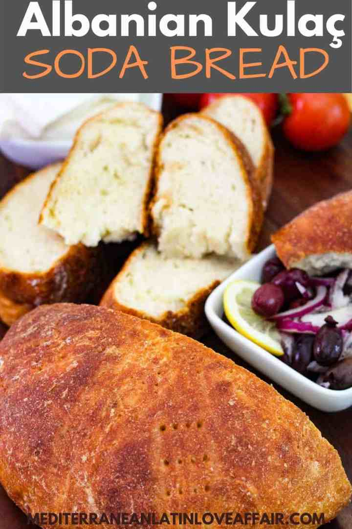 Homemade soda bread (Kulaç) shown cut in half, half is sliced and half is whole. Bread is next to mezes like olives and cheese.