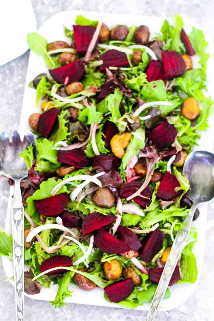 A rectangle shallow dish with a green salad that notably has beets, chestnuts and onions in it. Platter has 2 serving utensils on the side.