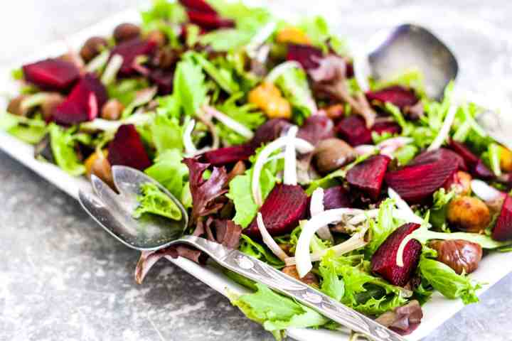 Beets and green salad topped with roasted chestnuts.