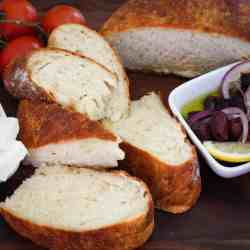 Sliced homemade bread shown with olives, tomatoes and cheese.