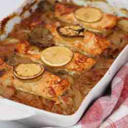 Baked dish with salmon and onions. Salmon is garnished with lemon.