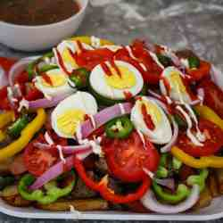 A platter with fries, meat, vegetables, eggs and sauces shown next to a large bowl of salsa.