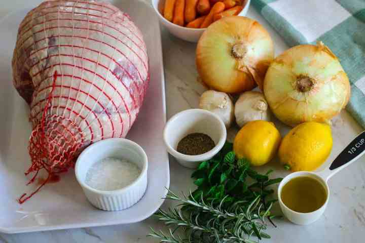 Ingredients lined up for cooking slow roasted lamb leg: lamb leg in a net, coarse salt, oregano, rosemary, mint, lemons, onions, olive oil, garlic and carrots.