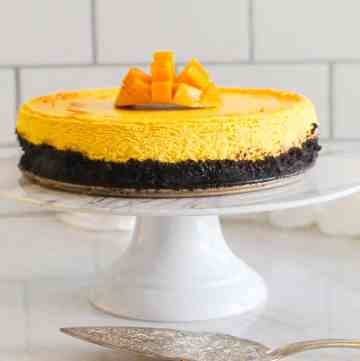 A mango cheesecake with oreo crust on a cake display. There's fresh mango cut on top of the cheesecake and a serving utensil