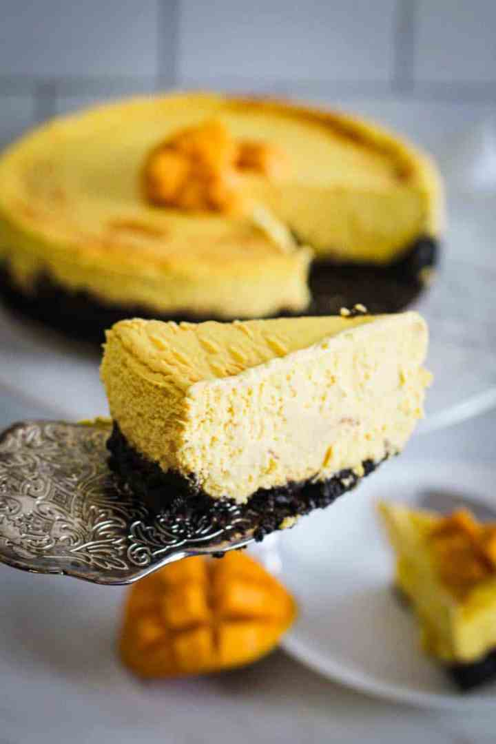 A slice of cheesecake up front and center. You see the cheesecake in the background and another slice already placed in a plate. There's fresh mango next to the plate.