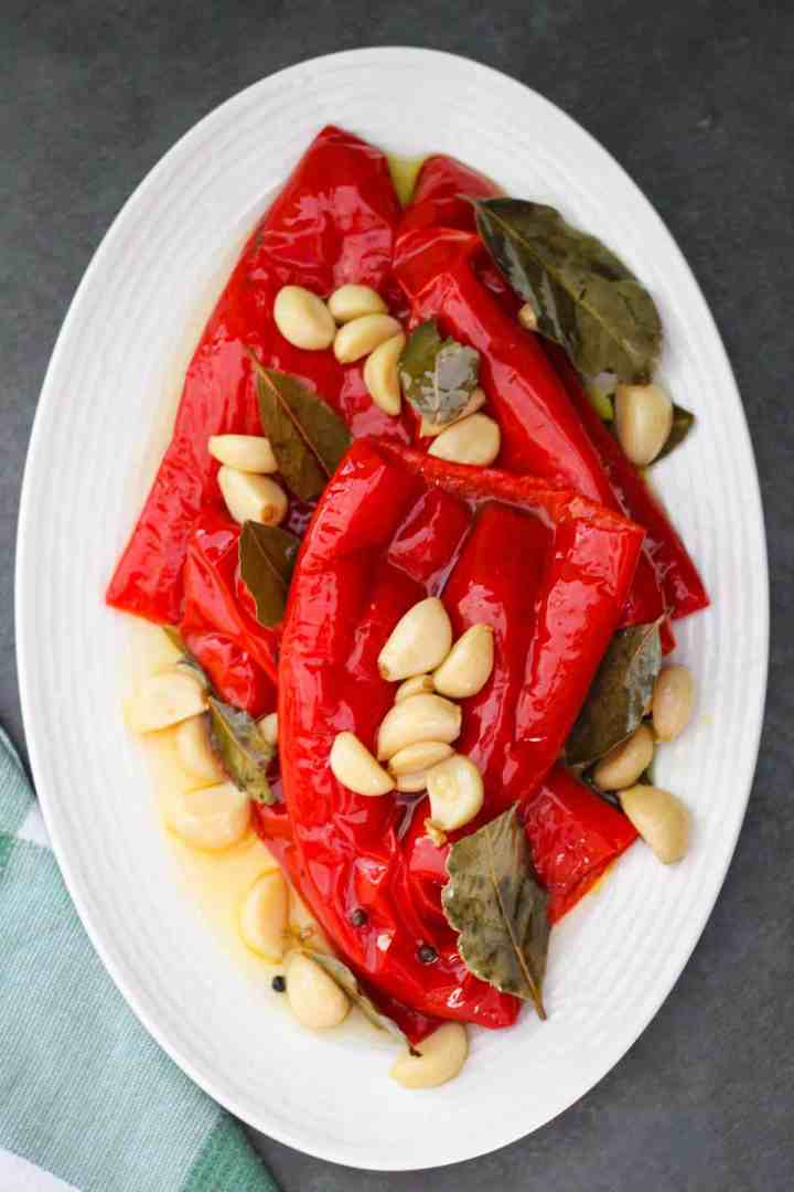 Albanian red peppers cooked in pressure cooker, they're called gogozhare. The peppers are shown served on a platter with garlic, pepper, and bay leaves.