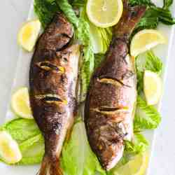 2 whole baked fish, Red Snapper on a platter with greens and lemons.