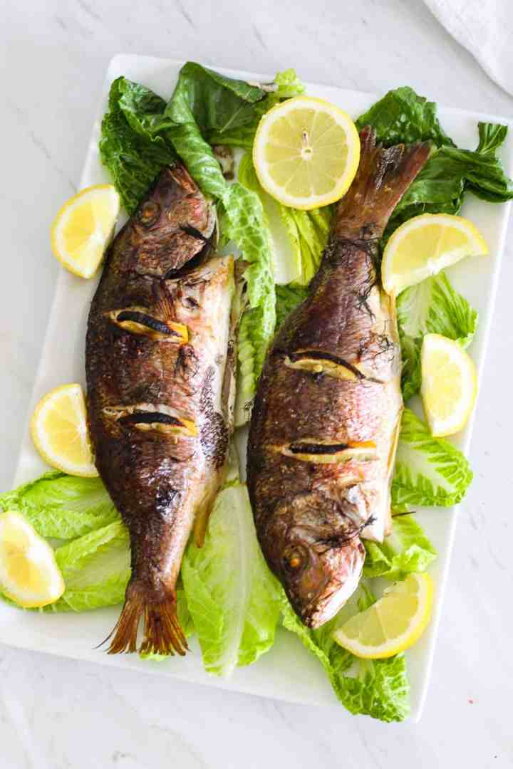A rectangular platter showing 2 baked whole red snappers, over lettuce and garnished with fresh lemon slices.
