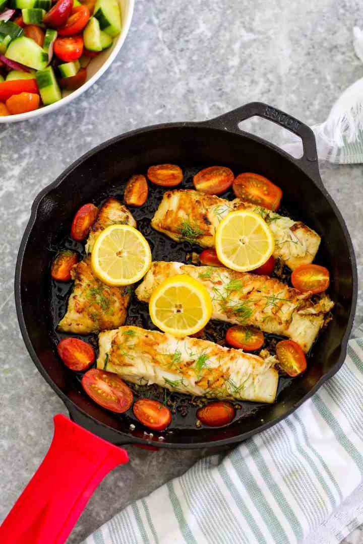 Seafood dinner with halibut fish - this dish is shown cooked on a cast iron skillet. There are 4 fish fillets in the skillet, lemon slices, cherry tomatoes and everything is garnished with dill.