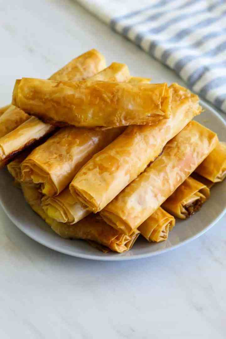 A plate with baked phyllo sticks. They look golden brown.