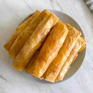 A pile of baked phyllo cheese sticks on a plate, view is from above.